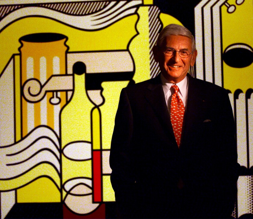 "Eli Broad stands in front of the Roy Lichtenstein painting ""Purist Still Life."""