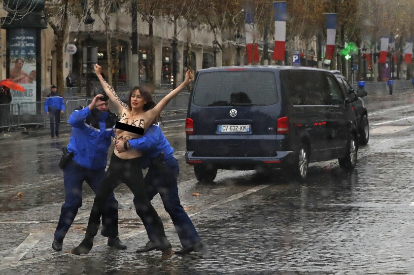 French police officers apprehend a topless protester who ran toward President Trump's motorcade in Paris on Sunday.