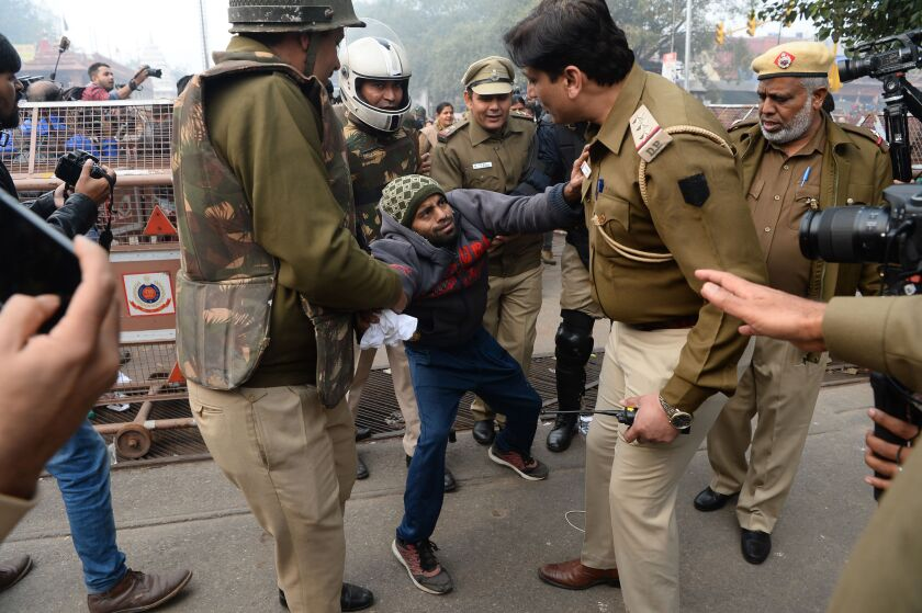 Police detain a man during a protest in New Delhi against India's new citizenship law.