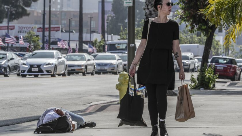 LOS ANGELES, CA, TUESDAY, JUNE 4 2019 - A pedestrian passes a woman sleeping on the sidewalk near t