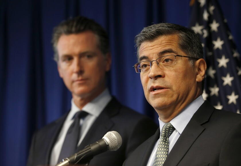 FILE - In this Sept. 18, 2019, file photo California Attorney General Xavier Becerra, right, flanked by Gov. Gavin Newsom, speaks during a news conference in Sacramento, Calif. California attorney general says he has been investigating Facebook's privacy practices since 2018. Becerra offered few details about the probe and said he was disclosing it only because his office was making a public court filing to force Facebook to answer its subpoenas, which Becerra said Facebook has failed to respond adequately do. (AP Photo/Rich Pedroncelli, File)