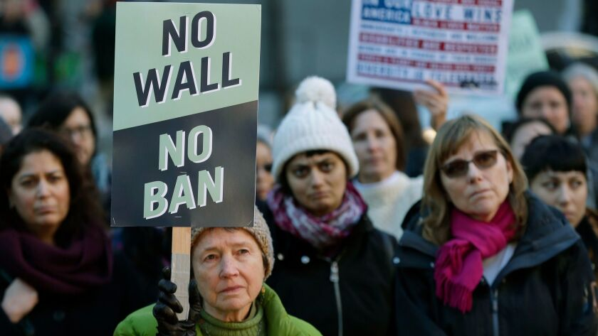 "Annie Phillips, of Burien, Wash., holds a sign that reads ""No Wall No Ban,"" during a protest, Wednes"