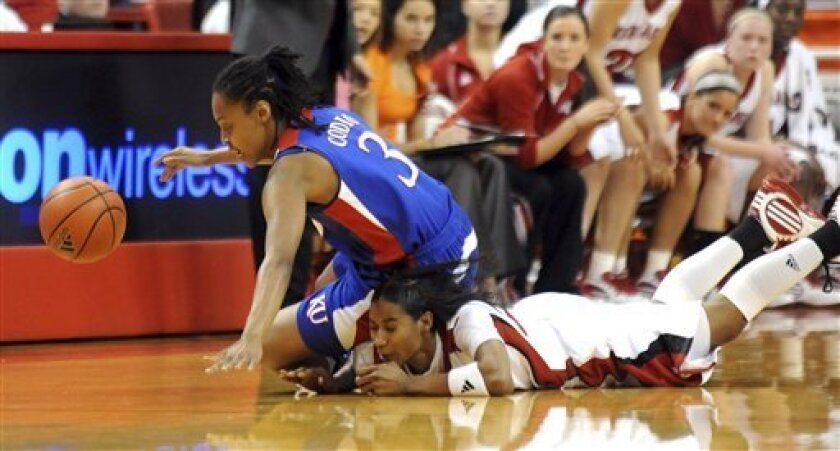 Kansas's Rhea Codio (3) lands on Nebraska's Yvonne Turner (22) while going for a loose ball during a Wednesday, March 3, 2010, NCAA college basketball game in Lincoln, Neb. (AP Photo/Dave Weaver)