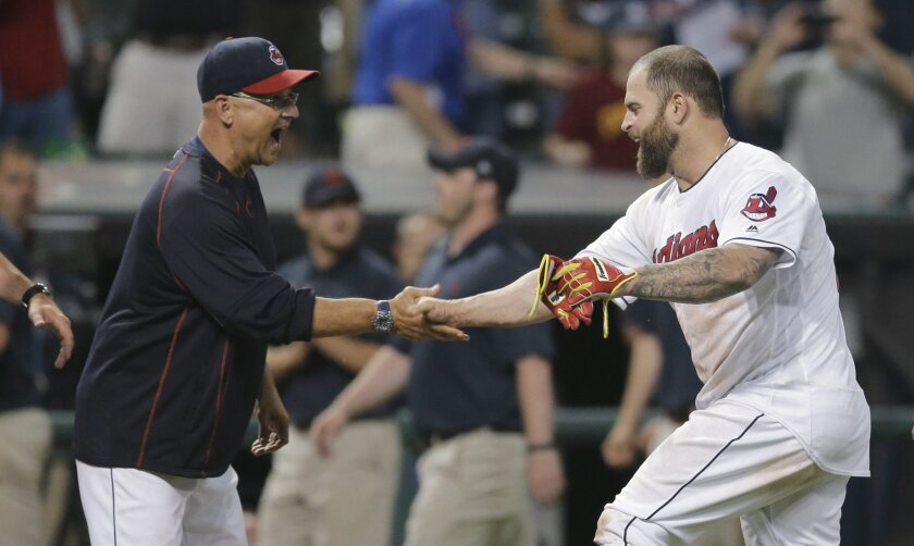 Cleveland Indians manager Terry Francona, left, congratulates Mike Napoli after Napoli hit a sacrifice fly that scored Francisco Lindor in the ninth inning of a baseball game against the Kansas City Royals, Thursday, June 2, 2016, in Cleveland. The Indians won 5-4. (AP Photo/Tony Dejak)