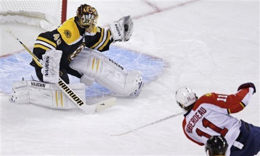 Boston Bruins goalie Tuukka Rask (40) gloves the puck on a shot by Florida Panthers center Jonathan Huberdeau (11) during the first period of an NHL hockey game in Boston, Thursday, March 14, 2013. (AP Photo/Charles Krupa)