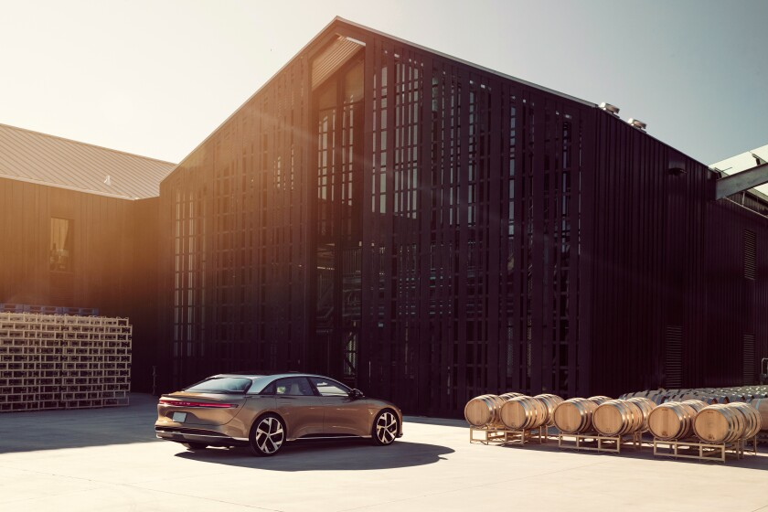 The Lucid Air shown at a winery with barn and barrels