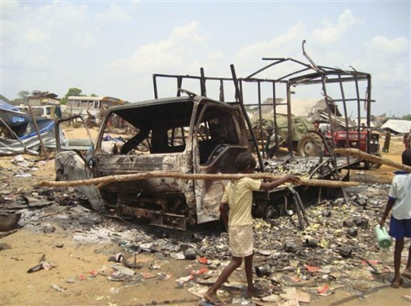 Sri Lankan ethic Tamil children walk past debris of burnt vehicles devastated allegedly by aerial bombing in the Tamil Tiger controlled no fire zone in Mullivaaykaal, Sri Lanka, Tuesday, May 5, 2009. (AP Photo)