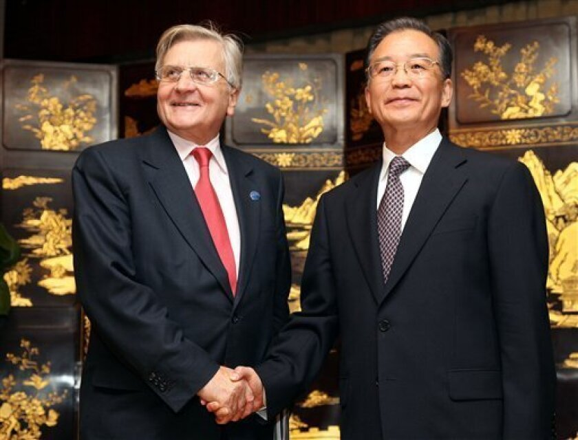 Chinese Premier Wen Jiabao, right, and European Central Bank President Jean-Claude Trichet shake hands before their meeting Sunday, Nov. 29, 2009 in Nanjing, China. (AP Photo/Eugene Hoshiko)