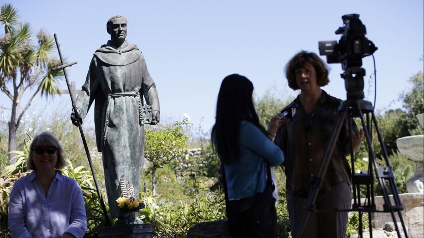 File - In this Sept. 23, 2015 file photo, an interview is conducted next to a statue of Junipero Ser