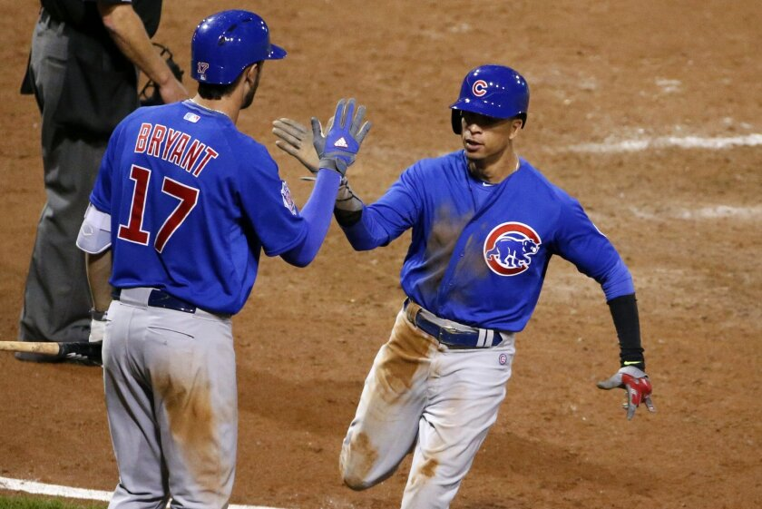 Chicago Cubs' Javier Baez, right, celebrates with Kris Bryant (17) after scoring from third on a sacrifice fly by Anthony Rizzo off Pittsburgh Pirates relief pitcher Vance Worley during the 12th inning of a baseball game in Pittsburgh, Wednesday, Sept. 16, 2015. (AP Photo/Gene J. Puskar)