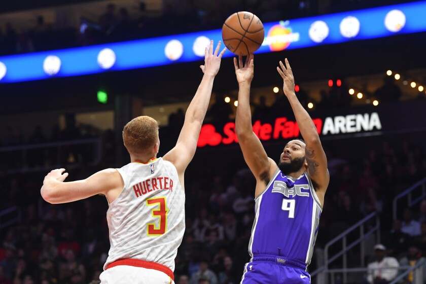 Sacramento Kings guard Cory Joseph (9) shoots as Atlanta Hawks guard Kevin Huerter (3) defends during the second half of an NBA basketball game Friday, Nov. 8, 2019, in Atlanta. The Kings won 121-109. (AP Photo/John Amis)