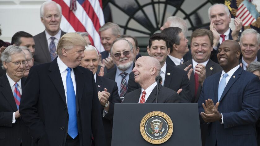 House Ways and Means Committee Chairman Kevin Brady (R-Texas), center, turns to President Trump in December as Republicans celebrated passage of last year's tax cut bill. Brady is pushing follow-up legislation that would make the temporary individual tax cuts permanent.