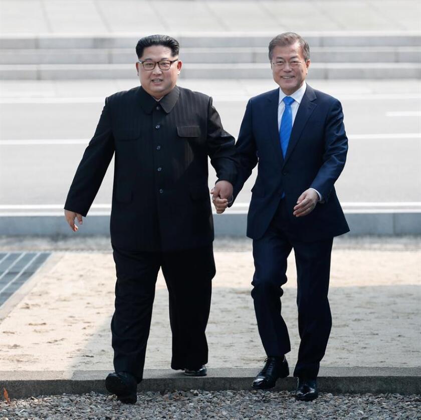 El presidente surcoreano, Moon Jae-in (d), y el líder del Norte, Kim Jong-un (i), caminan tomados de la mano en la línea de demarcación militar (MDL), durante una ceremonia de bienvenida en el lado sur de la frontera militarizada que separa a ambos países, antes de iniciar su histórica cumbre hoy, viernes 27 de abril de 2018, en la aldea de Panmunjom en Paju (Corea del Sur). EFE/KOREA SUMMIT PRESS POOL/POOL