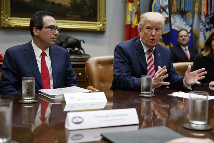 Treasury Secretary Steve Mnuchin listens as President Donald Trump speaks during a meeting on tax policy with business leaders in the Roosevelt Room of the White House on Oct. 31, 2017.
