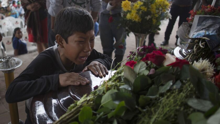 A youth cries over the coffin of Nery Otoniel Gomez Rivas, 17, whose body was pulled from the volcan
