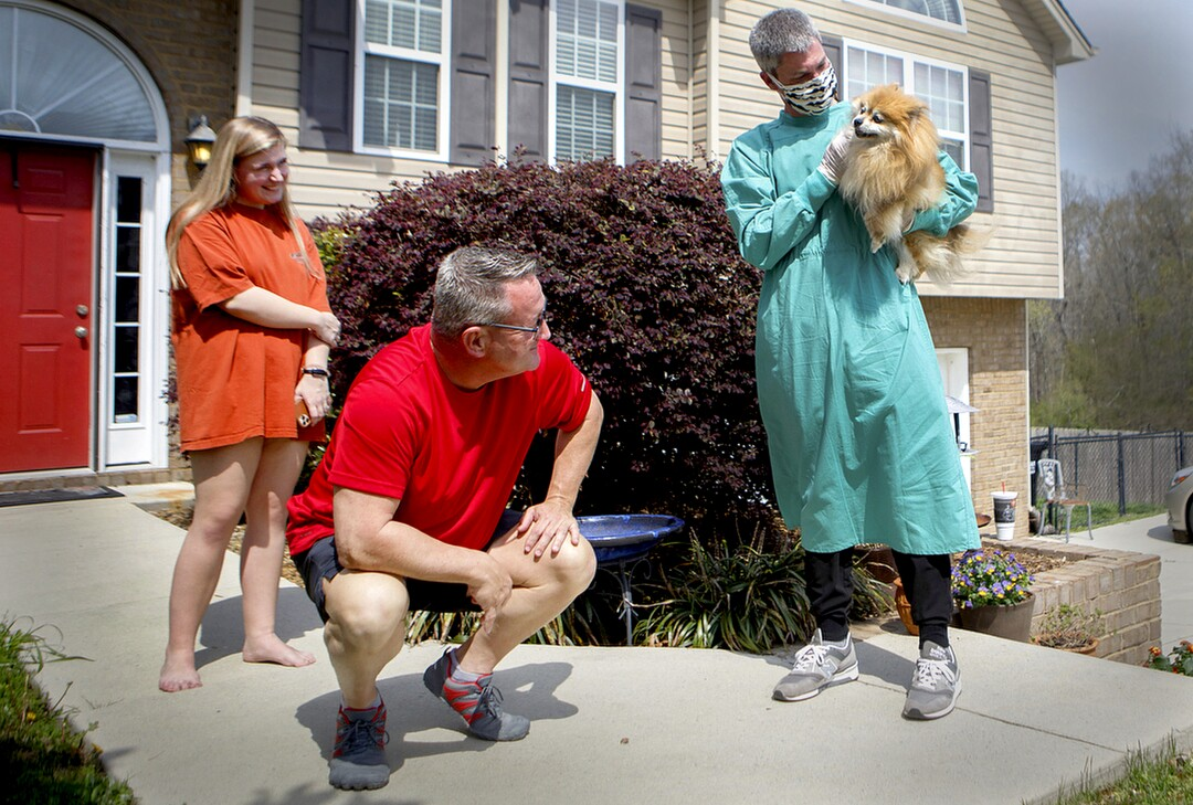 U.S.: Ooltewah Veterinary Hospital Dr. Micah Woods holds Izzy as owners Ken, center, and Zoe Leslie look on at the Leslies' home March 27 in Ooltewah, Tenn. Because of the coronavirus outbreak, Ooltewah Veterinary Hospital began to offer house calls for clients who are unable to leave their homes.