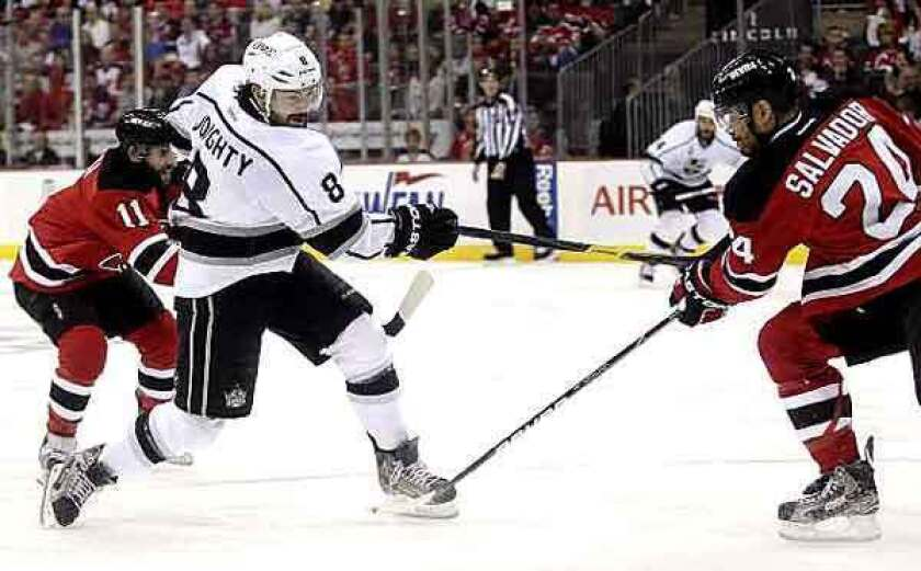 Kings defenseman Drew Doughty follows through on a shot that zipped past Devils defenseman Bryce Salvador and beat goaltender Martin Brodeur (not pictured) in the first period of Game 2 on Saturday evening at the Prudential Center in Newark, N.J.