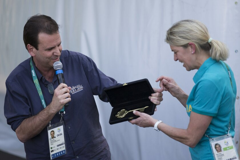 Rio de Janeiro's mayor Eduardo Paes, left, hands the City's Key to Australia's delegation head Kitty Chiller during a ceremony at the Olympic Village in Rio de Janeiro, Brazil, Wednesday, July 27, 2016. (AP Photo/Felipe Dana)