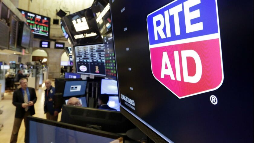 The logo for Rite Aid is displayed above a trading post on the floor of the New York Stock Exchange,