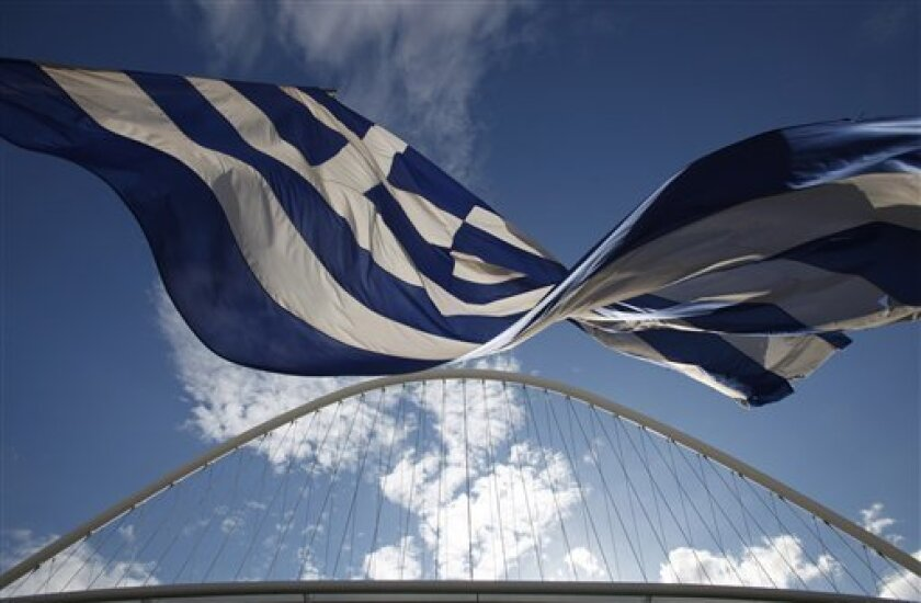 In this photo taken on May 17, 2010, a Greek flag waves next to the metal arch over the velodrome at the Athens main Olympic complex. Olympic officials deny that massive spending for the 2004 Games in Athens contributed to the country's financial crisis. (AP Photo/Petros Giannakouris)