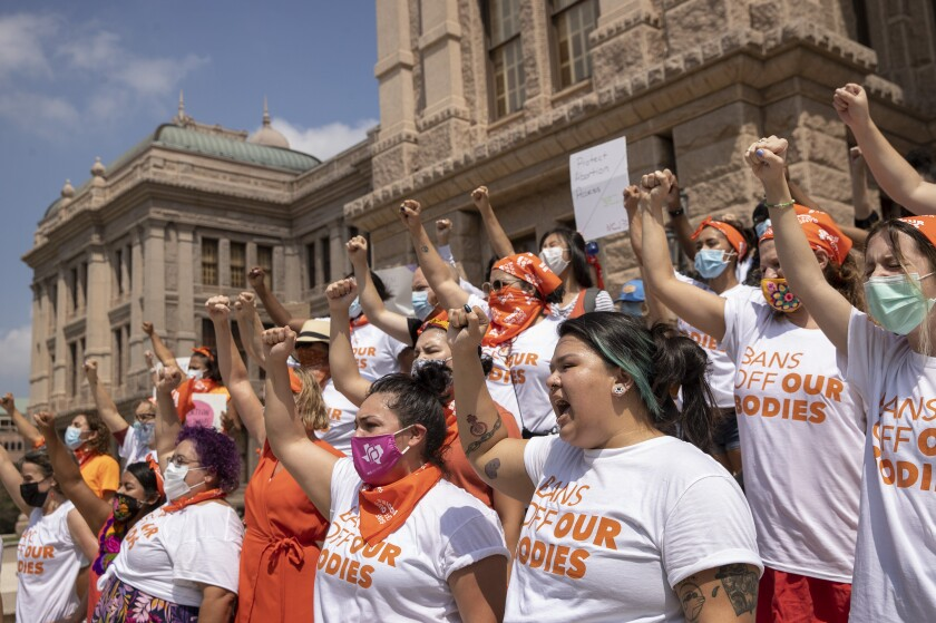 """Women wearing """"Bans Off Our Bodies"""" shirts raise fists and chant at the Texas Capitol."""
