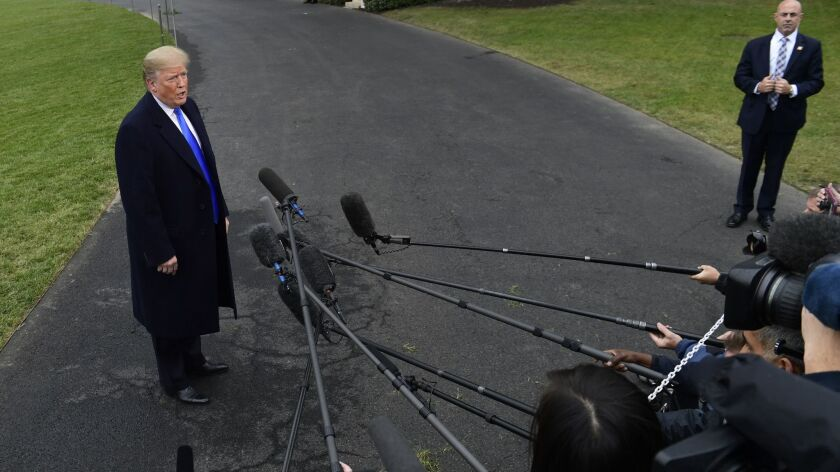 President Trump talks with reporters at the White House on Friday.