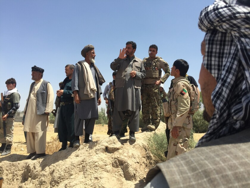 Yasin Zia, governor of Takhar province in Afghanistan, center, talks to militiamen outside Eshkamesh, Afghanistan, in July.