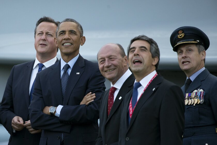 From left, British Prime Minister David Cameron, U.S. President Barack Obama, Romanian President Traian Basescu, Bulgarian President Rosen Plevneliev and British RAF Group Captain David Bentley watch a flypast on the second day of a NATO summit at the Celtic Manor Resort in Newport, Wales on Friday, Sept. 5, 2014. (AP Photo/Matt Dunham)