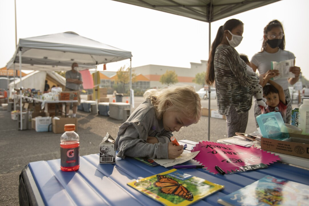 Cheyenne Brewer, age 7, who lost her home in the Almeda fire, colors at a donation center in Phoenix, Ore.