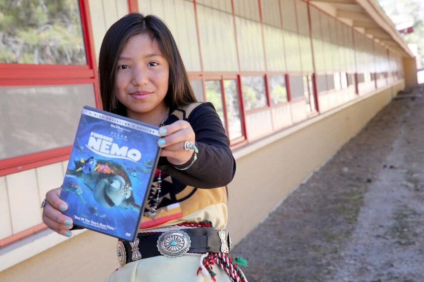 "In this Thursday, March 17, 2016 photo, Mikyla Hongeva, 11, holds a copy of ""Finding Nemo"" outside the Peunte de Hozho elementary school in Flagstaff, Ariz. Mikyla recorded the voice of one of the turtles in the Navajo language version of the movie, only the second major motion picture to be translated. ""Star Wars Episode IV: A New Hope"" became the first Hollywood feature dubbed in Navajo in 2013. (Jake Bacon/Arizona Daily Sun via AP)"