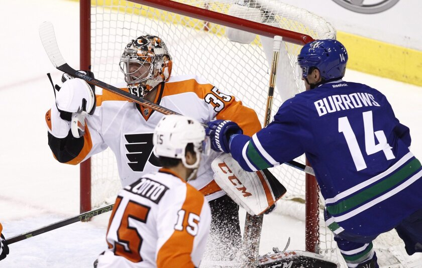 Vancouver Canucks' Alex Burrows (14) is stopped by Philadelphia Flyers goaltender Steve Mason during the second period of an NHL hockey game in Vancouver, British Columbia, Monday, Nov. 2, 2015. (Ben Nelms/The Canadian Press via AP) MANDATORY CREDIT