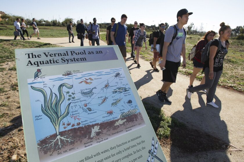 Miramar College professor Basam Barkho's general biology class walks past an interpretive sign at the vernal pools trail at the college campus Tuesday.
