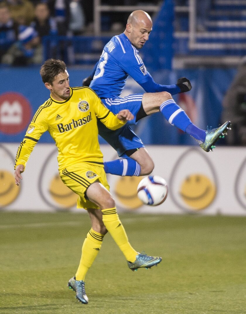Montreal Impact's Laurent Ciman, right, challenges Columbus Crew SC's Ethan Finlay during first half of an MLS soccer game in Montreal, Sunday, Nov. 1, 2015. (Graham Hughes/The Canadian Press via AP) MANDATORY CREDIT