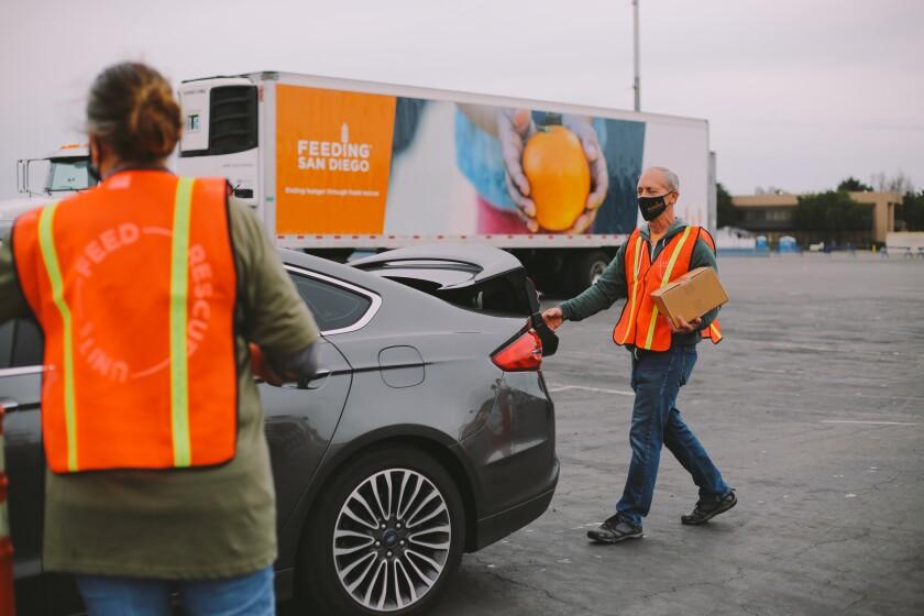 Los voluntarios de Feeding San Diego entregan cajas de alimentos en los vehículos.