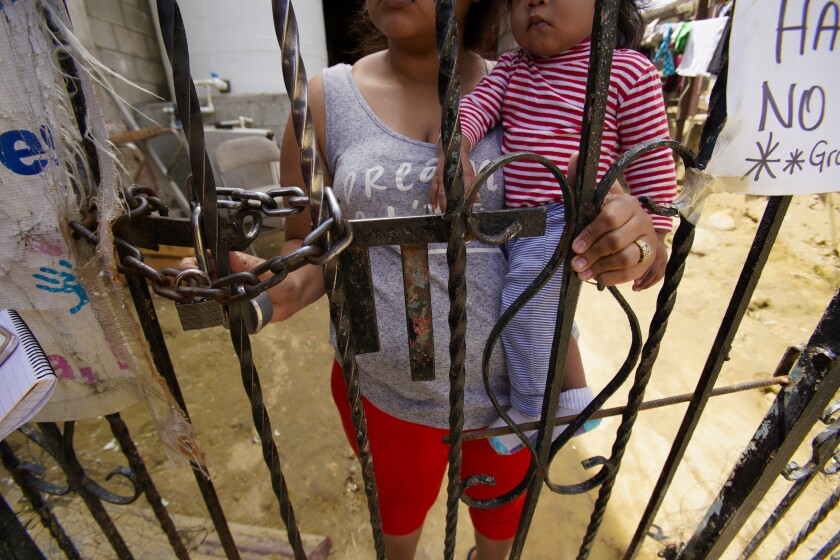A mother (prefers not to give her name) along with her youngest of two children waits at the front entrance of the Embajadores shelter in Tijuana on June 27, 2019. She recently arrived in Tijuana a week ago with her 5-year old son and her 7-month old baby, where she spent several nights on the street before moving into the shelter. She claims she had to leave Honduras because the gangs in Honduras are threatening her because her husband who is in the U.S., refuses to join the gang.