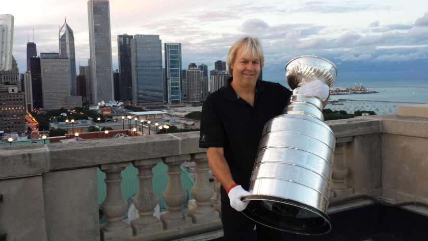 With the Chicago skyline behind him, Stanley Cup caretaker Philip Pritchard holds up hockey's most-coveted trophy.