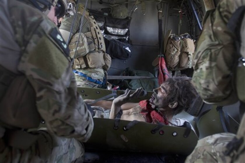 An Afghan soldier looks down to see his badly injured leg, which was blown off in an IED explosion, as he is cared for in the back of a helicopter by pararescuemen from the U.S. Air Force 46th Expeditionary Rescue Squadron in Afghanistan's Kandahar province on Friday, Oct. 8, 2010. (AP Photo/David Guttenfelder)