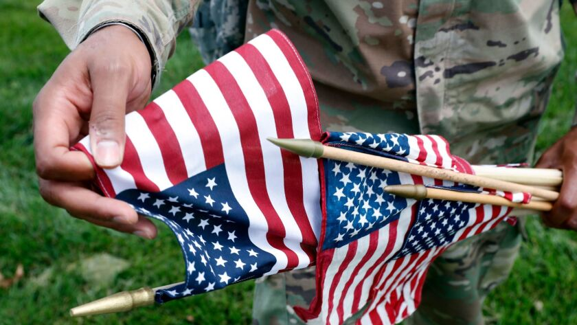 U.S. Army Staff Sgt. Anthony Ellis with the 3d U.S. Infantry Regiment (The Old Guard), grabs a flag