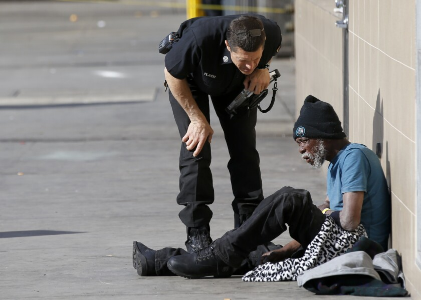 A Los Angeles Fire Department paramedic speaks with a homeless man who was too weak to stand.