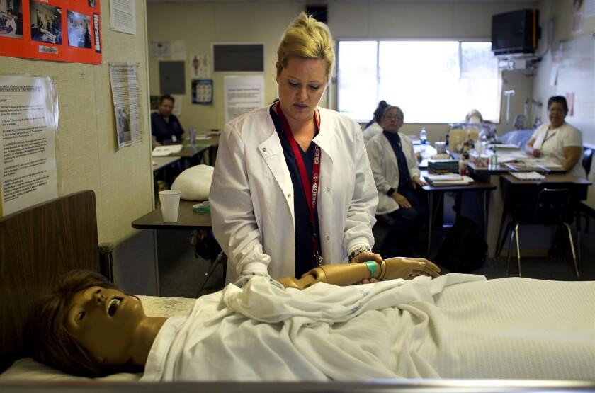 Nursing student Tiffany Bonham with a dummy patient