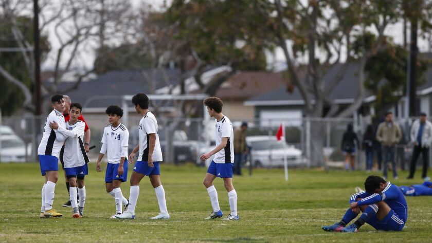 Central players celebrate their win as a Chula Vista player hangs his head on the field.