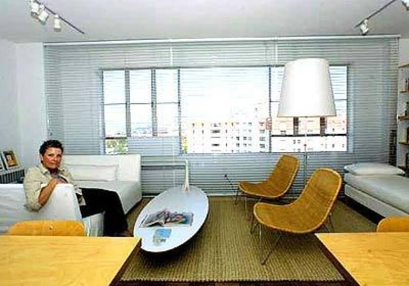 """Jackie Terrell, 57, """"started over with IKEA"""" after her divorce. Renting in Park La Brea for the third time, she chose a 12th floor unit, repainted the walls her favorite shade of white and decided on an airy, modern, informal look throughout."""