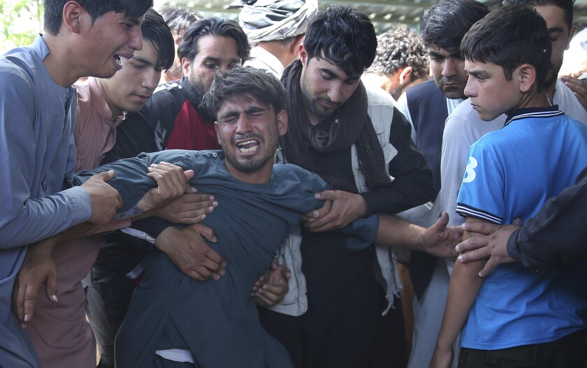 Relatives grieve over victims of Afghanistan wedding hall blast