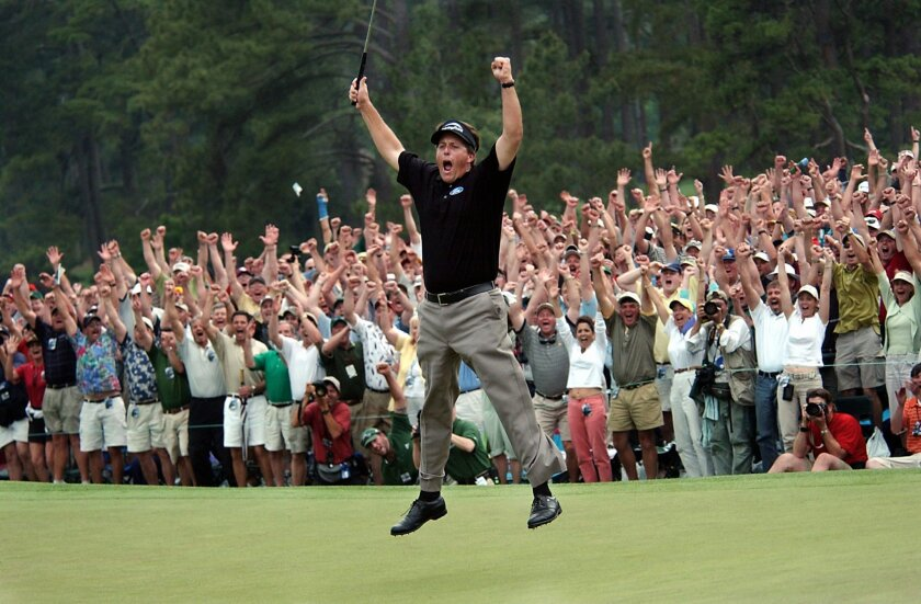 FILE - In this April 11, 2004, file photo, taken by Dave Martin,  Phil Mickelson celebrates after winning the Masters golf tournament with at the Augusta National Golf Club in Augusta, Ga. Martin, a longtime Associated Press photographer based in Montgomery, Ala., died after collapsing on the Georg