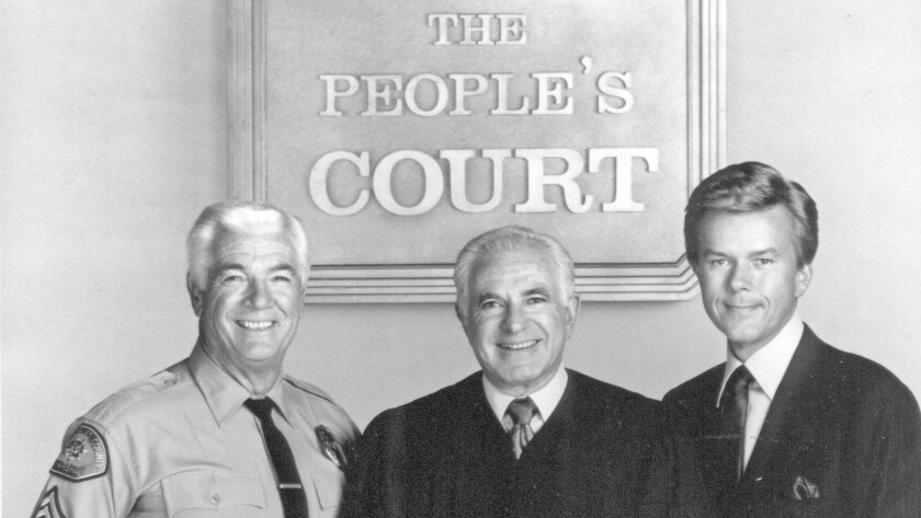 "Judge Joseph A. Wapner, center, poses with Bailiff Rusty Burrell and Court Reporter Doug Llewelyn in a 1992 promotion photo for the 9th season of ""The People's Court."""