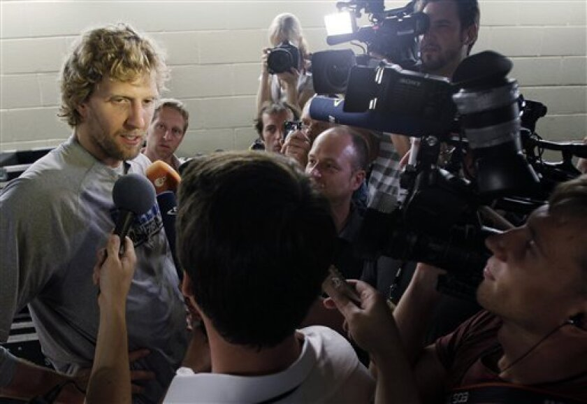 Dallas Mavericks' Dirk Nowitzki, left, answers questions for the media after a basketball practice for Game 5 of the NBA finals against the Miami Heat, Wednesday, June 8, 2011, in Dallas. The series is tied 2-2. (AP Photo/Mark Humphrey)