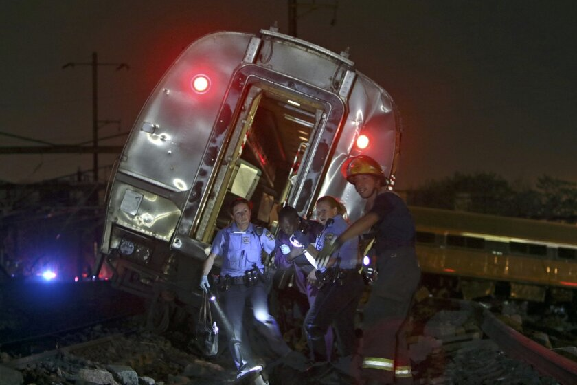 FILE - In this May 12, 2015 file photo, emergency personnel work the scene of a deadly train wreck in Philadelphia. An Amtrak train headed to New York City derailed and crashed in Philadelphia. Senate Democrats are demanding more money for Amtrak so the railroad can tackle a $21 billion backlog in repair and replacement projects. They say that backlog compromises safety and service.(AP Photo/ Joseph Kaczmarek)