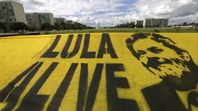 Demonstrators place a banner in support of former Brazil President Luiz Inacio Lula da Silva, at the