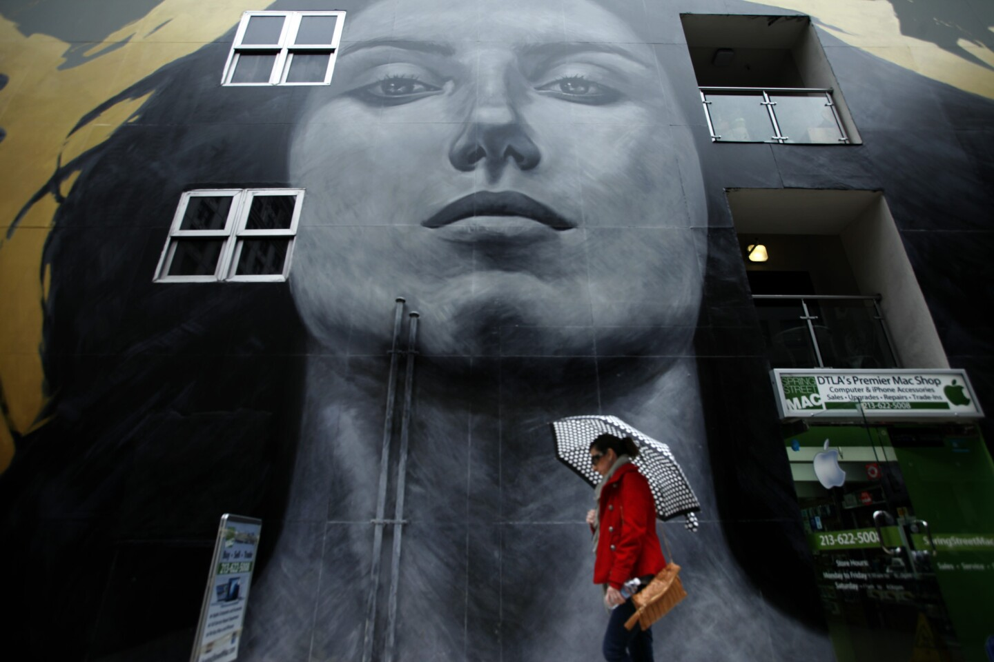 """Ana Fuentes makes her way through the rain and walks past the mural by Robert Vargas and Michael Blaze entitled, """"Our Lady of DTLA,"""" that graces the SB Tower building at 6ht and Spring Streets People in downtown Los Angeles."""