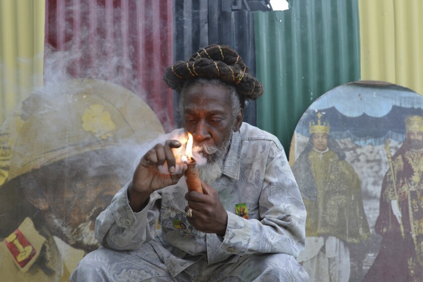 "FILE - In this Aug. 28, 2014 file photo, legalization advocate and reggae legend Bunny Wailer smokes a pipe stuffed with marijuana during a ""reasoning"" session in a yard in Kingston, Jamaica. Wailer, a reggae luminary who was the last surviving member of the legendary group The Wailers, died on Tuesday, March 2, 2021, in his native Jamaica, according to his manager. He was 73. (AP Photo/David McFadden, File)"